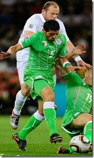 Wayne Rooney is tackled by Rafik Halliche